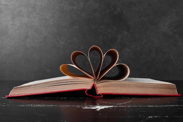 Un libro abierto con páginas envueltas.
