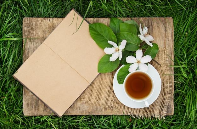 Un libro abierto con páginas vacías, una taza de té caliente y una flor de membrillo.