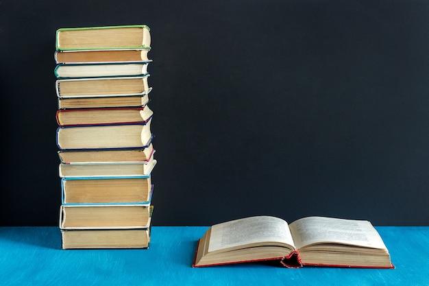 Libro abierto y pila de libros.