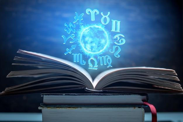 Libro abierto sobre astrología. el resplandeciente globo mágico con signos del zodiaco en la luz azul.
