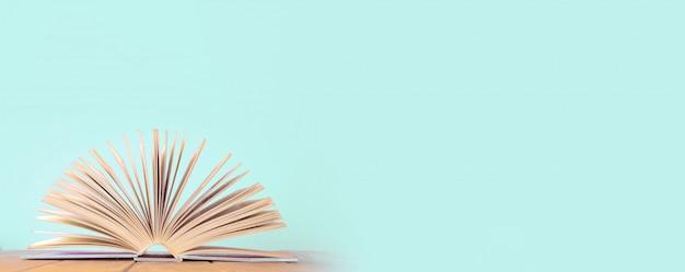 Libro abierto sobre la mesa de madera sobre fondo azul.