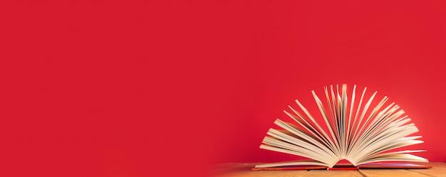 Libro abierto sobre la mesa de madera sobre fondo rojo.