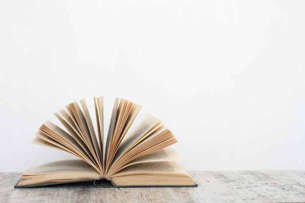 Libro abierto sobre una superficie de madera con el fondo de una pared blanca