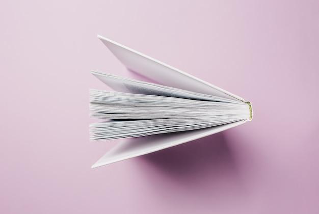 Libro abierto sobre una superficie rosa