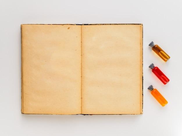Un libro abierto y viales de vidrio con diferentes elixires para usar en magia y adivinación. espacio para texto.