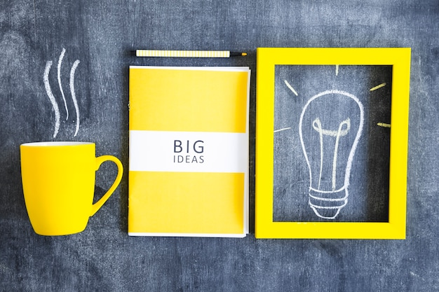 Libro amarillo de grandes ideas; marco de bombilla y taza de café en la pizarra