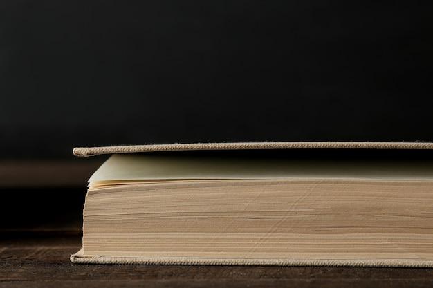 El libro ampliado se cierra sobre una mesa de madera marrón y sobre un fondo negro. libros viejos. educación. colegio. estudio...