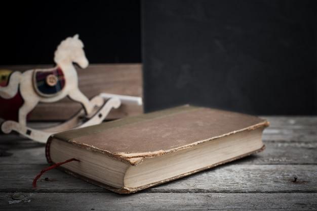 Libro antiguo y caballo de juguete de madera.