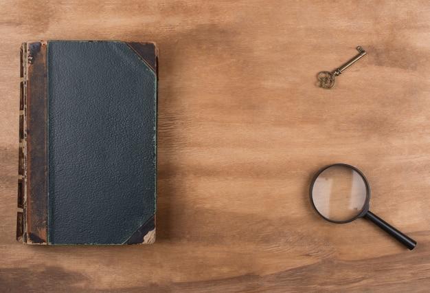 Libro antiguo, una llave y una lupa.