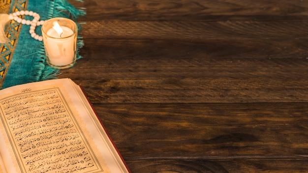 Libro árabe abierto cerca de cuentas y vela