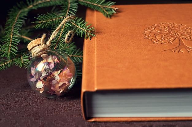 Libro bajo el árbol de navidad decorado con bola de cristal.