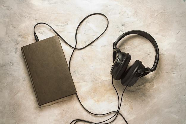 Libro y auriculares conectados a él en una piedra blanca
