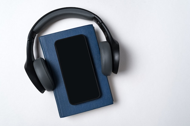 Libro azul, auriculares y teléfono. concepto de libros electrónicos y audiolibros. fondo blanco copia espacio.