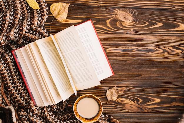 Libro y bebida cerca de bufanda y hojas