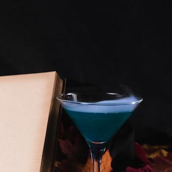 Libro con bebida sobre fondo negro