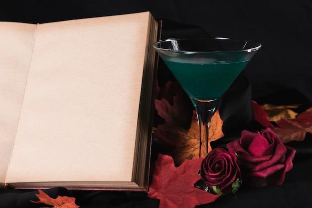 Libro con bebida verde y rosas