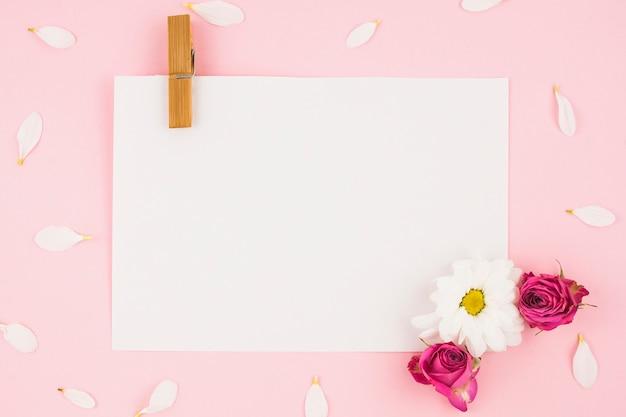 Libro blanco en blanco con pinza para la ropa y flores sobre fondo rosa