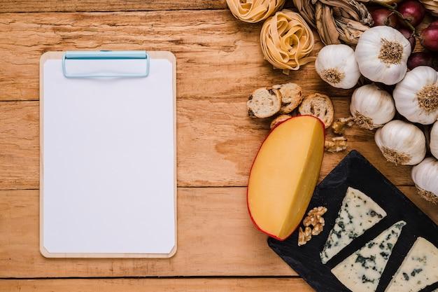 Libro blanco en blanco en el portapapeles cerca de ingredientes saludables en el escritorio