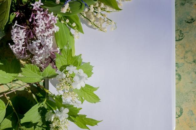 Libro blanco en blanco sobre una mesa de madera con flores de primavera
