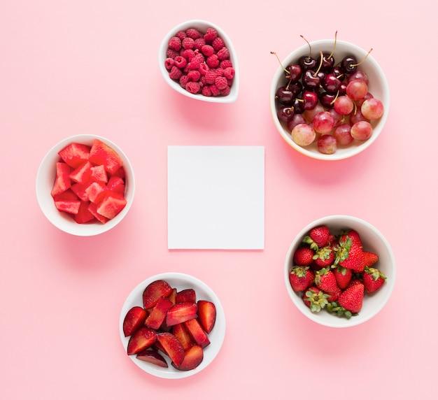 Libro blanco en blanco con tazones de frutas de color rojo sobre fondo rosa