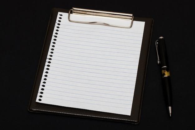 Libro blanco y bolígrafo sobre mesa negra