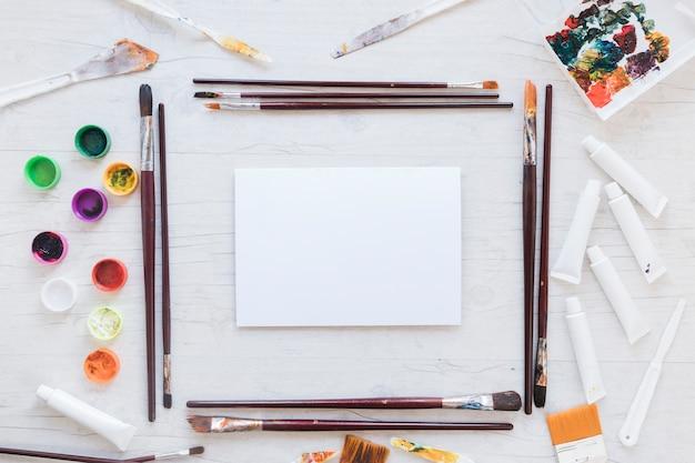 Libro blanco cerca de pinceles, gouache y cuchillos para el arte.