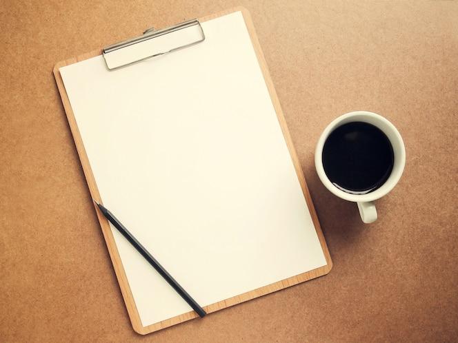 Libro blanco en blanco en el portapapeles con taza de café, efecto de filtro retro