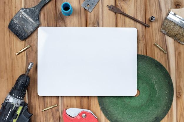 Libro blanco y herramientas manuales en piso de madera.