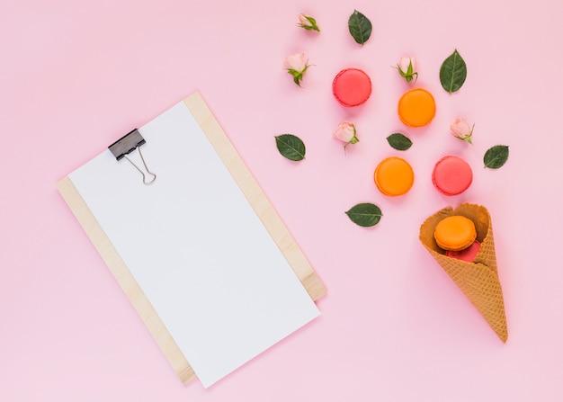 Libro blanco en el portapapeles con macarrones de colores sobre el cono de waffle con fondo rosa