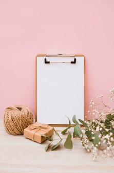 Libro blanco sobre portapapeles con carrete; caja de regalo y flores de aliento de bebé en el escritorio de madera con fondo rosa
