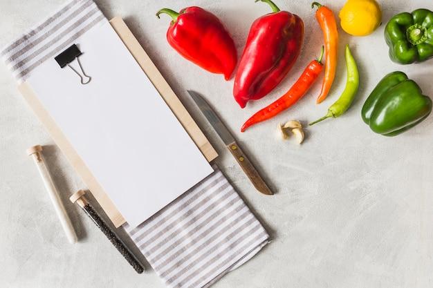 Libro blanco sobre portapapeles con verduras; cuchillo; tubo de ensayo de sal y pimienta negra.