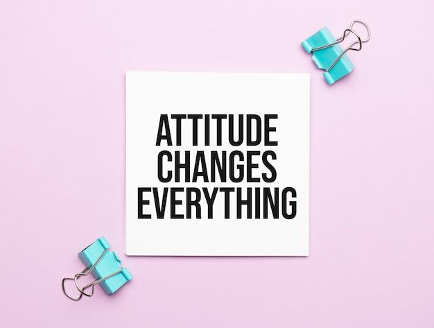 Libro blanco con texto la actitud cambia todo sobre un fondo amarillo con papelería