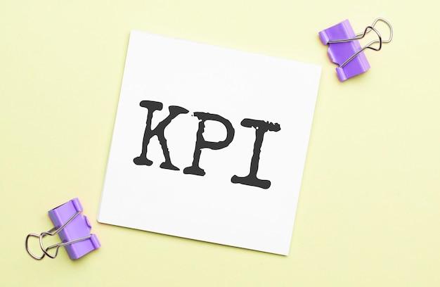 Libro blanco con texto kpi sobre fondo amarillo con papelería