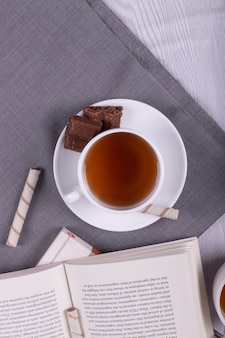 Libro, bocadillos dulces y una taza de té sobre la mesa.