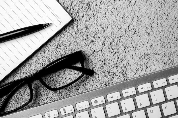 Libro, bolígrafo y gafas en el escritorio de hormigón. - por concepto creativo y empresarial.