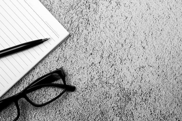 Libro, bolígrafo y gafas en el escritorio de hormigón. - para el fondo del concepto creativo y empresarial.