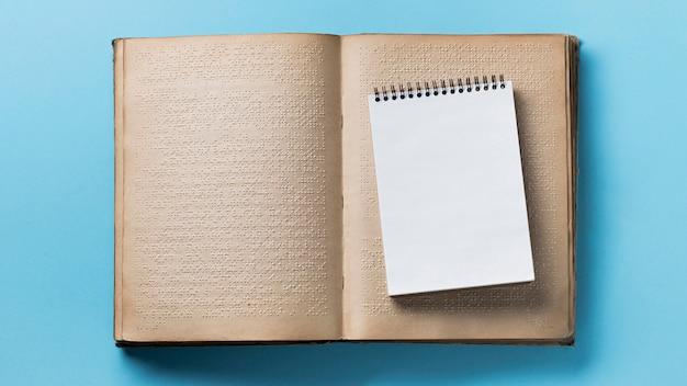 Libro en braille plano laico sobre fondo azul
