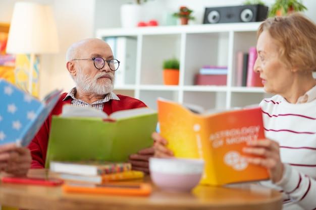 Libro se calienta. agradables personas mayores que se miran mientras disfrutan leyendo diferentes libros
