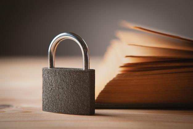 Libro y candado en una mesa de madera, conocimiento oculto Foto Premium