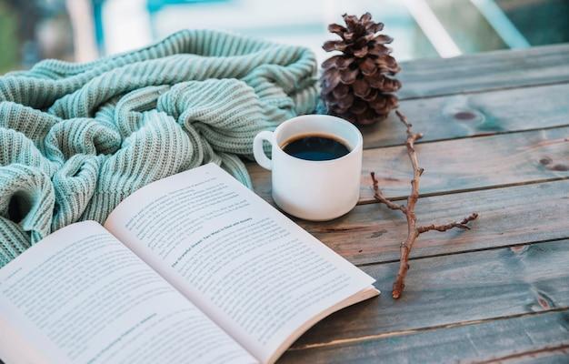 Libro cerca de taza y textil de lana en mesa.