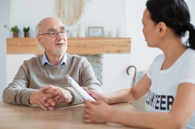 Libro controvertido. voluntario sosteniendo el libro mientras se comunica con un atractivo hombre mayor agradable y mirándolo