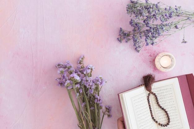 Libro del corán con flores de color púrpura