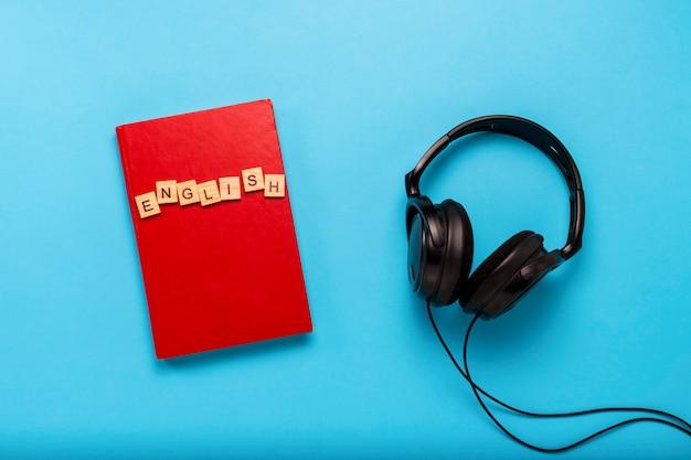 Libro con una cubierta roja con texto inglés y auriculares negros sobre fondo azul. concepto de audiolibros, autoeducación y aprendizaje de inglés de forma independiente. vista plana, vista superior