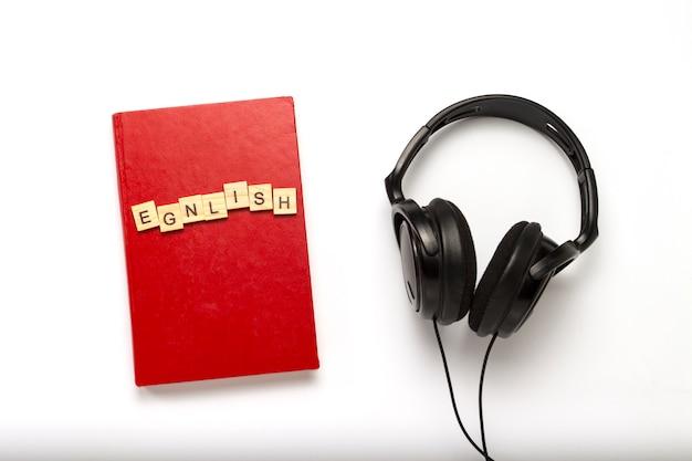 Libro con una cubierta roja con texto inglés y auriculares negros sobre un fondo blanco. concepto de audiolibros, autoeducación y aprendizaje de inglés de forma independiente. vista plana, vista superior