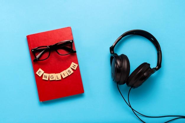 Libro con una cubierta roja con texto en inglés, gafas y auriculares negros sobre un fondo azul. concepto de audiolibros, autoeducación y aprendizaje de inglés de forma independiente. vista plana, vista superior