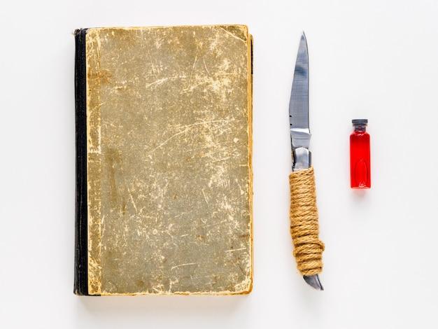 Libro, cuchillo y ampolla con sangre sobre un fondo blanco. establecido para la magia.