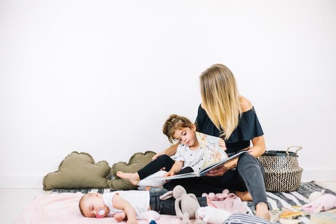 Libro de lectura de mujer y niña cerca de bebé