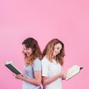 Libro de lectura sonriente de la mujer que se coloca de nuevo para apoyar contra el contexto rosado