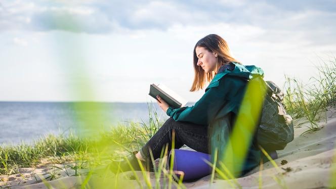 Libro de lectura turístico joven cerca del mar