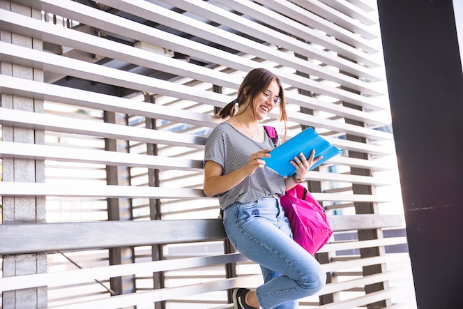 Libro de texto de lectura femenino alegre cerca de la pared